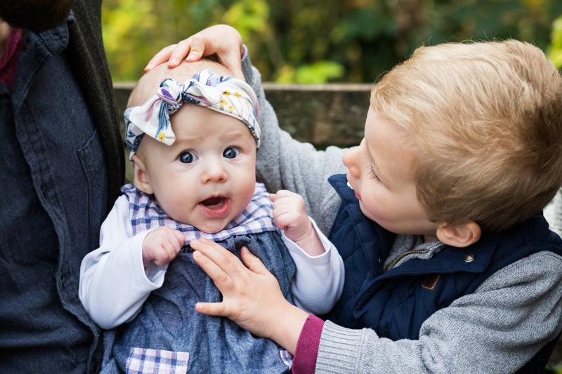 little boy holding baby girl's head