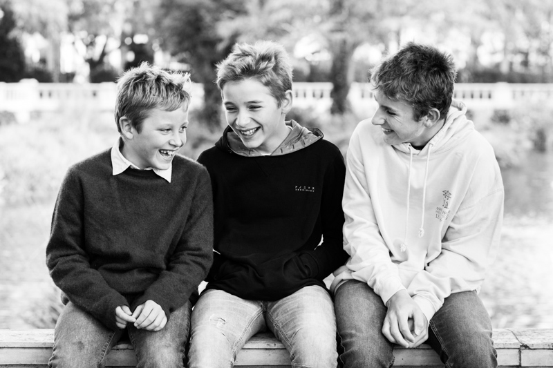 three boys sitting together laughing