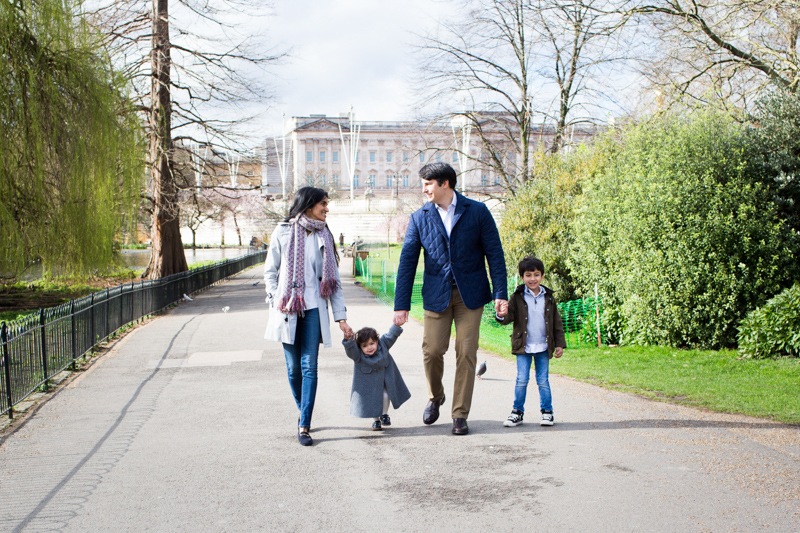 family of four walking in front of Buckingham Palace