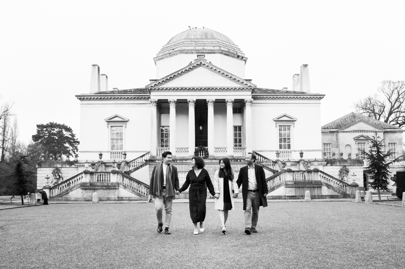 family of four walking hand in hand in front of beautiful building