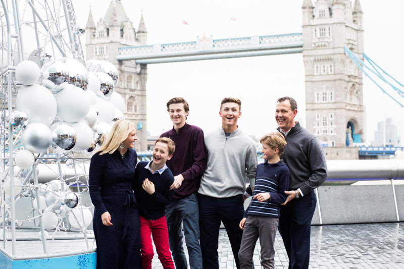 Lady, man and four boys standing in front of Tower Bridge