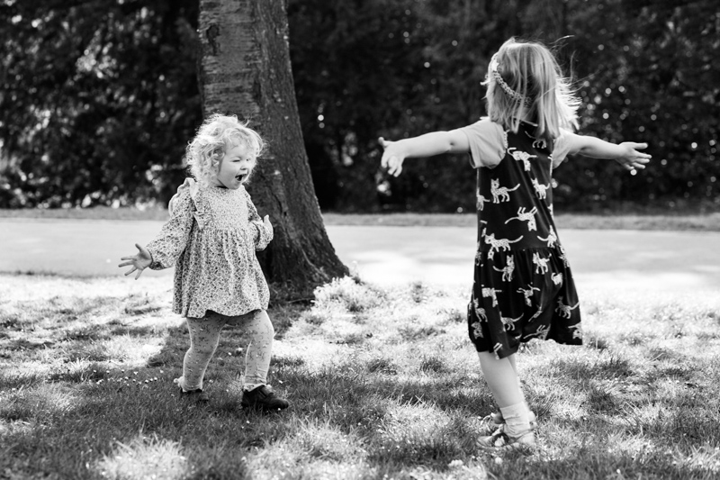 two little girls running towards each other with outstretched arms