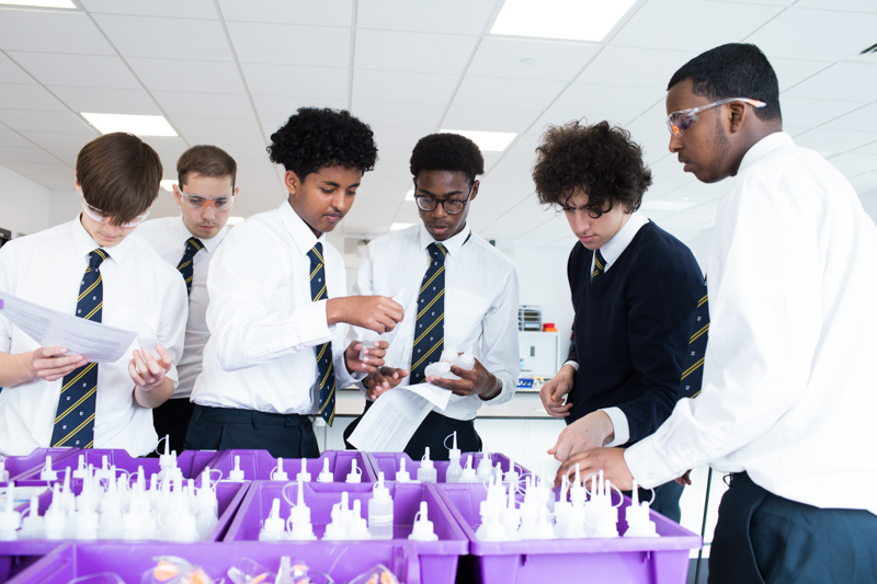 Six schoolboys getting science supplies in the classroom.