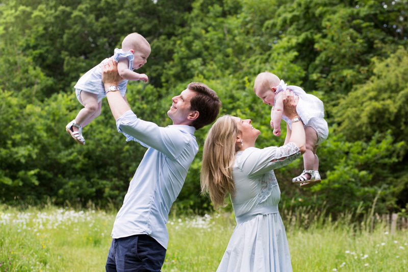 A man and lady holding up their baby twins in front of some trees.